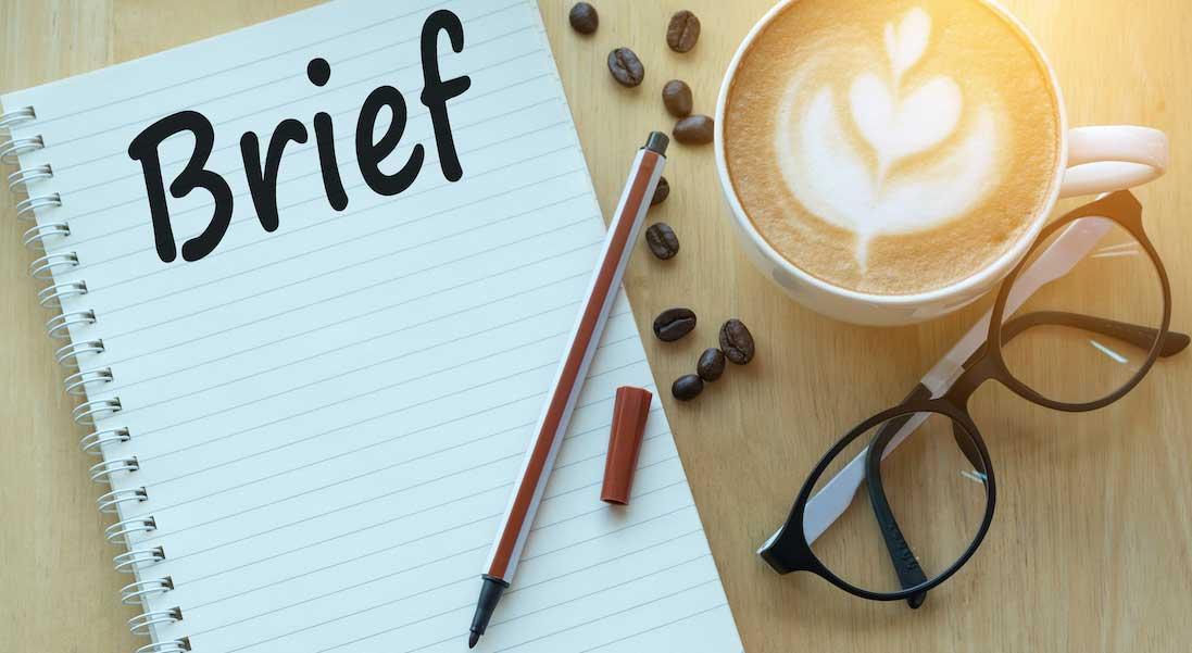 Concepto de Briefing para una agencia de marketing digital. Libreta, bolígrafo gafas y café sobre tabla de madera